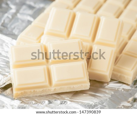 Tablet diced white chocolate on silver paper - stock photo