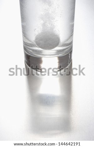 Tablet dissolving in glass of water - stock photo