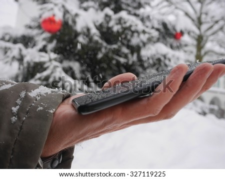 tablet in hand in winter smartphone winter christmas snow - stock photo