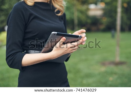 tablet in hand of the woman, city, business