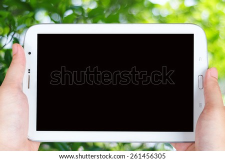 Tablet in hand over the blue tree with bokeh light background - stock photo