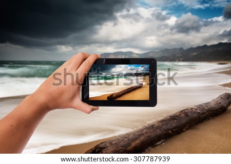 Tablet in hand photo shooting bad wheather on a beach in winter - these are all photos made by me, that you separately can find on my shutterstock portfolio. - stock photo