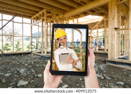 Tablet in hands and building a new home. Planning with the tablet on the construction site. - stock photo