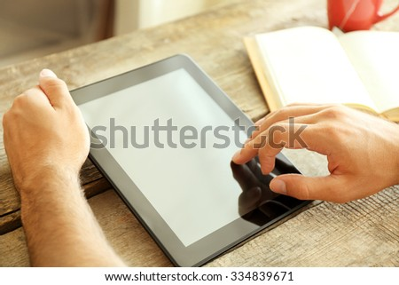 Tablet in man's hands, book and cup of tea on wooden table - stock photo