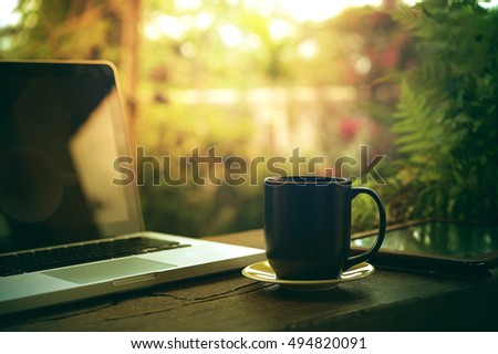 tablet laptop and black coffee cup on wood in cafe