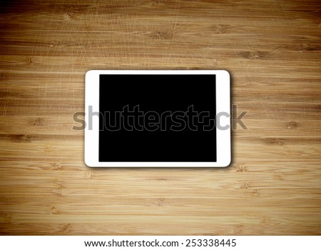 Tablet lying on the table with blank screen - stock photo