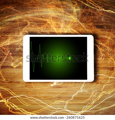 Tablet lying on the table with EKG on screen - stock photo