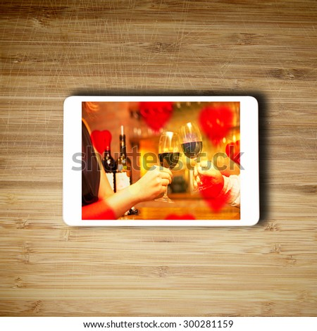 Tablet lying on the table with valentine's day concept screen - stock photo