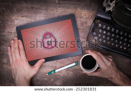 Tablet on a desk, concept of data protection, red - stock photo