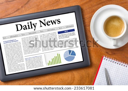 Tablet on a desk - Daily News - stock photo