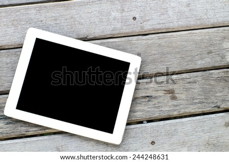Tablet on wooden background. - stock photo