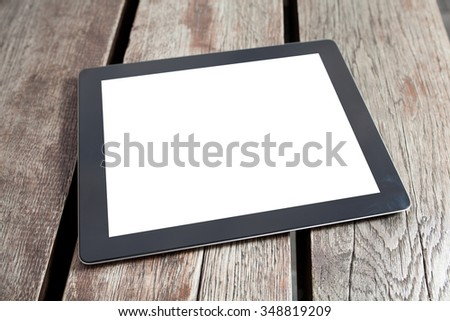 tablet pc computer gadget with isolated screen on a wooden background  - stock photo