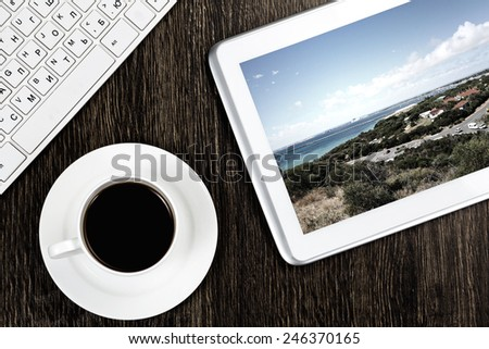 Tablet pc cup of coffee and keyboard at table - stock photo