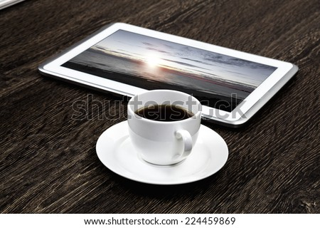 Tablet pc cup of coffee and notepad at table - stock photo