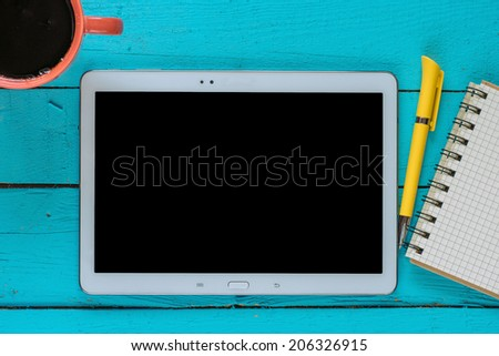 Tablet pc cup of coffee and notepad at table,morning news - stock photo
