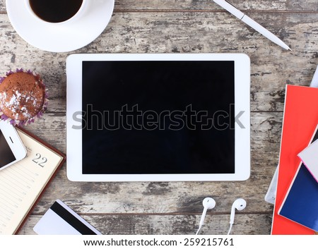 Tablet pc cup of coffee and notepad at wooden table - stock photo