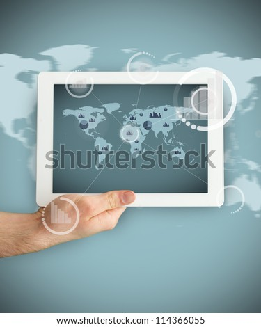 Tablet PC held by hand  showing a business world map