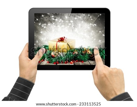 tablet pc in hands with christmas wallpaper. Choosing gift concept