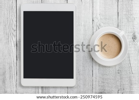 Tablet pc looking like ipad mini on table with coffee cup  - stock photo