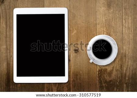Tablet pc looking like ipad on table with coffee cup
