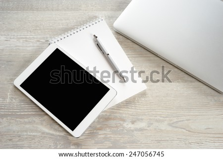 Tablet PC on a white table with a keyboard and a laptop - stock photo