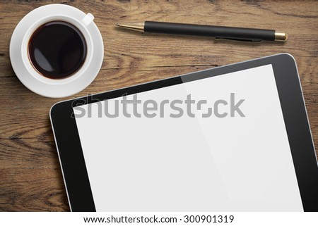 Tablet pc on table desk with coffee cup and pen top view - stock photo