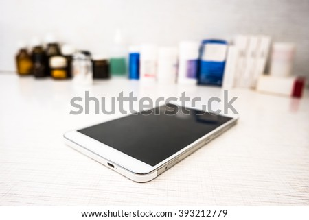 Tablet pc on white table  with medical objects on background as an image for electronic diagnostic or healthcare mobile apps. Medical background - stock photo
