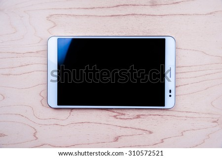 Tablet PC on wooden background with empty black screen. Gadget on a table - background for variety of themes, thechnology, blogging or web applications. - stock photo