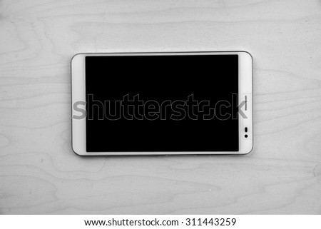 Tablet PC on wooden background with empty black screen. Gadget on a table - background for variety of themes, technology, blogging or web applications. - stock photo