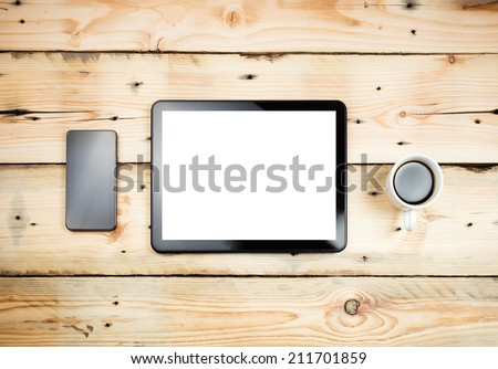 Tablet pc on wooden table - stock photo
