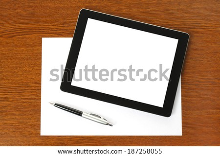Tablet PC, paper and pen on wooden background