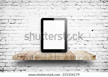 Tablet pc same with ipade on wooden shelf over white brick background - stock photo