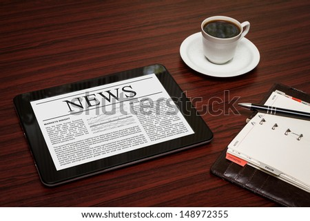 Tablet PC shows latest news on screen, which lying on work place.  - stock photo