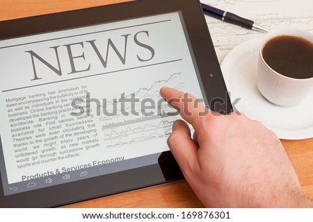 Tablet PC shows latest news on screen, which lying on work place.