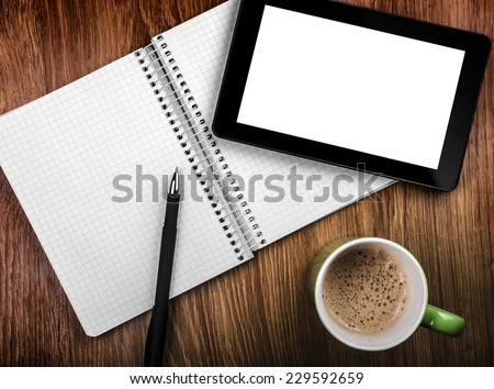 Tablet pc with an empty screen in hands close to a pen and green cup - stock photo