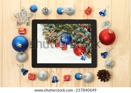 Tablet PC with Christmas decorations on wooden background  - stock photo