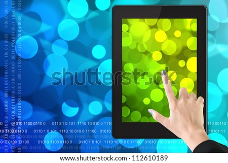 Tablet pc with hand point on blue blurred bokeh background.