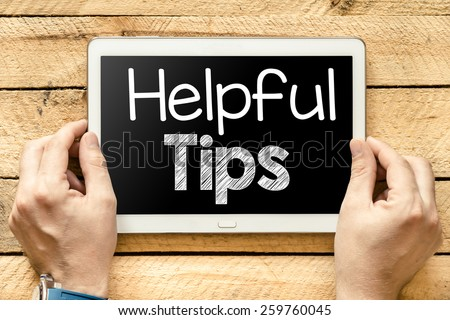 Tablet pc with helpful tips. Male hands holding tablet pc with helpful tips on wooden background - stock photo