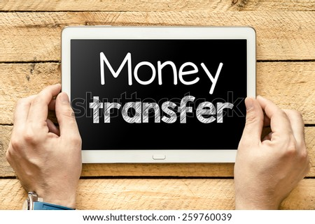 Tablet pc with money transfer. Male hands holding tablet pc with money transfer on wooden background - stock photo