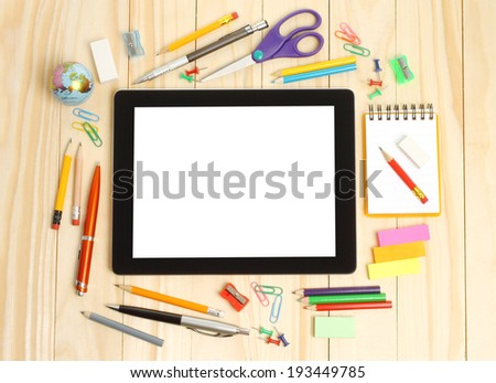 Tablet PC with school office supplies on wooden background   - stock photo