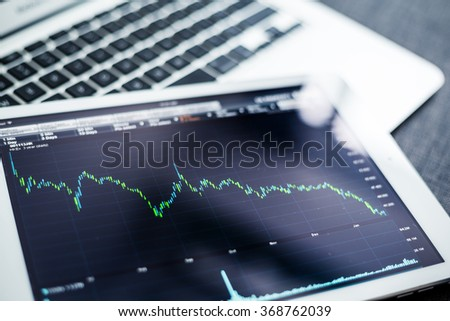 Tablet pc with stock exchage data - stock photo