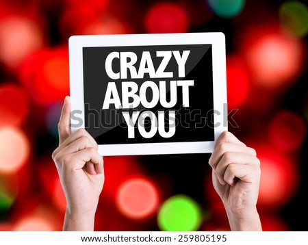 Tablet pc with text Crazy About You with bokeh background  - stock photo