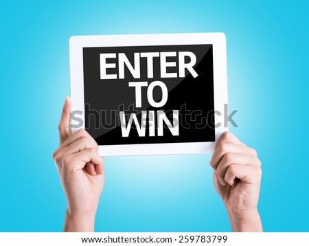 Tablet pc with text Enter to Win with blue background - stock photo