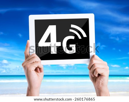 Tablet pc with text 4G with beach background - stock photo