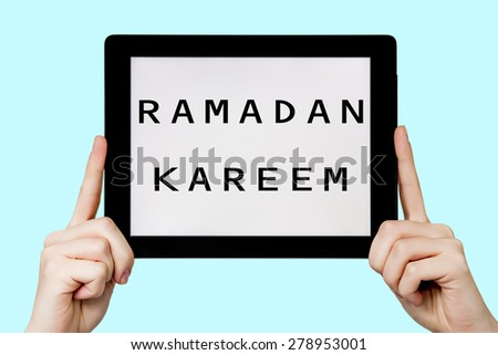 Tablet pc with text Ramadan kareem with blue background - stock photo