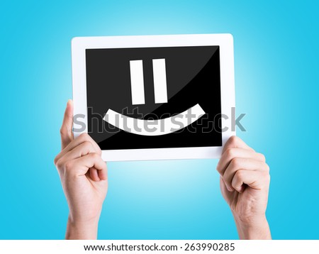 Tablet pc with text Smiley Face with blue background - stock photo