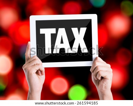 Tablet pc with text Tax with bokeh background - stock photo