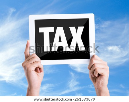 Tablet pc with text Tax with sky background - stock photo