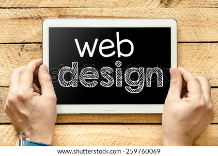 Tablet pc with web design. Male hands holding tablet pc with web design on wooden background - stock photo