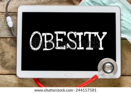 Tablet pc with word Obesity. Tablet pc with word Obesity and stethoscope, medicine concept - stock photo